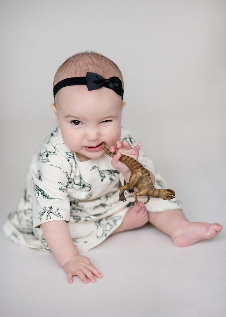 Little toddler girl holding a dinosaur, winking at the camera