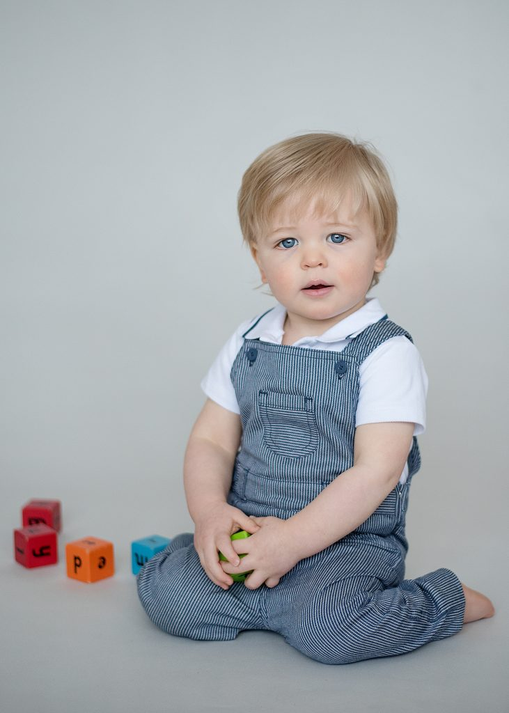Toddler sat upright in blue dungarees with play bricks