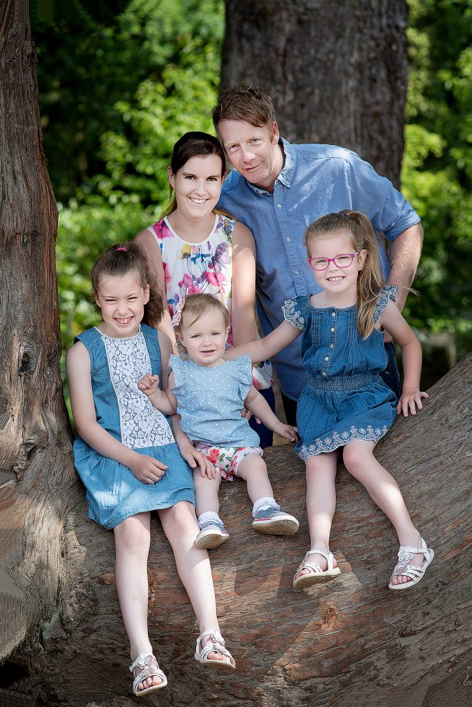 Family all pose for a professional photoshoot outdoors in a park