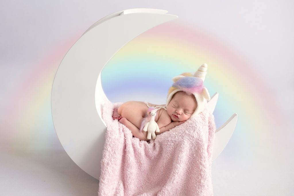 little baby sleeping in a moon dressed as a unicorn
