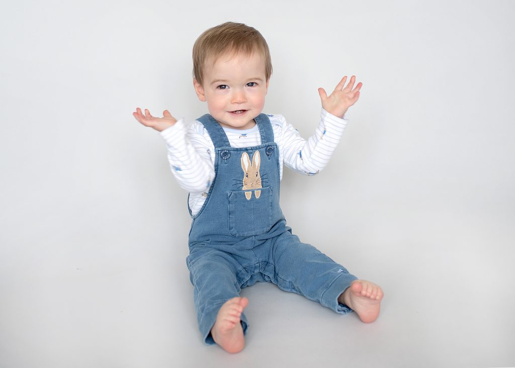 cute older baby in dungarees sitting up with hands in the air