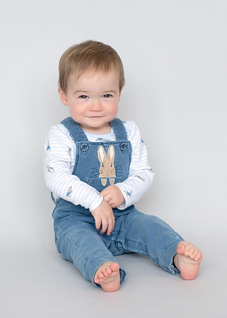 Little boy in peter rabbit dungarees in a photo studio in Northern Ireland