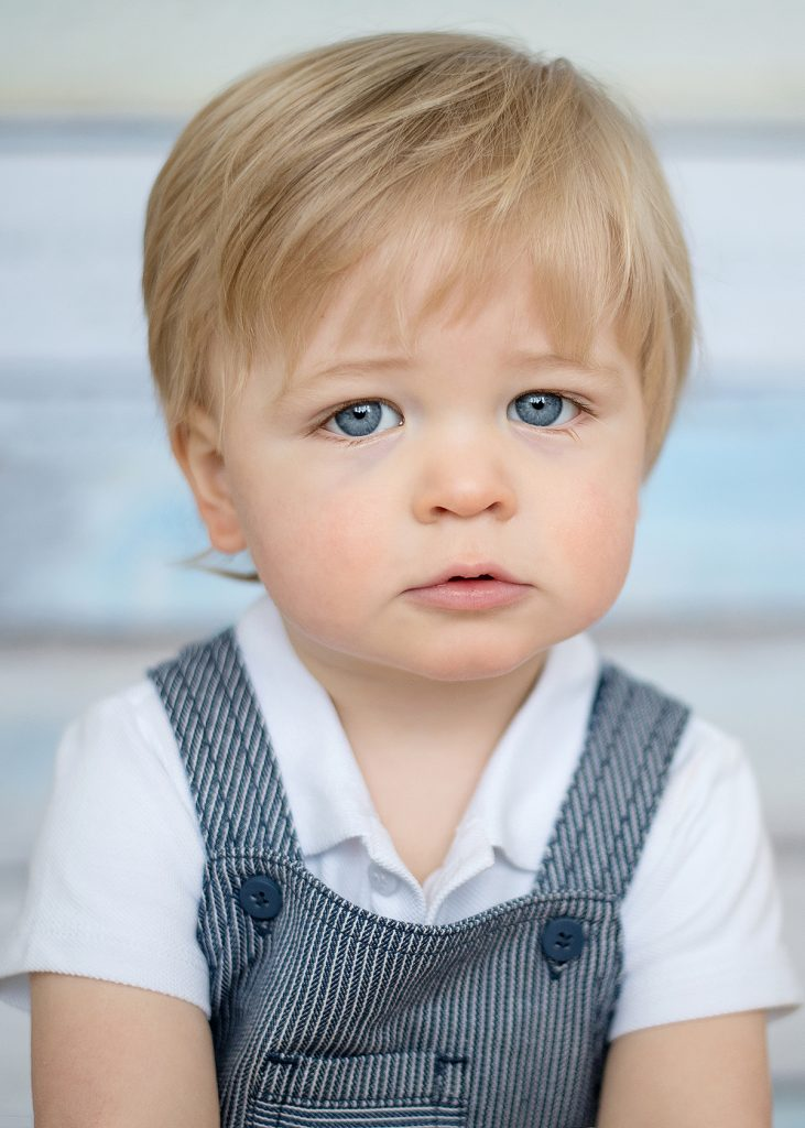 little boy with blue eyes and blonde hair, wearing dungarees