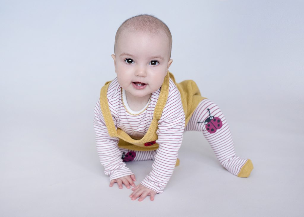 little girl wearing a yellow dress with stripey tights