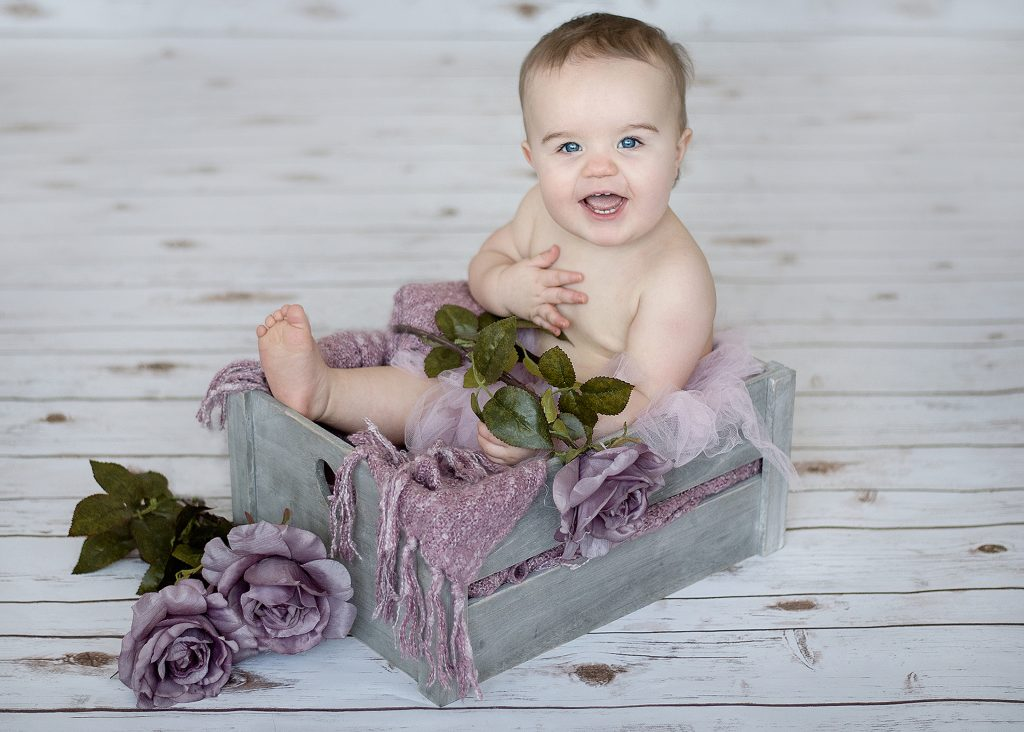 little baby sat in a fashionable wooden crate with purple decor