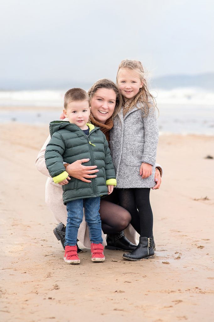 A cold day on the beach for mother and her two children in Northern Ireland