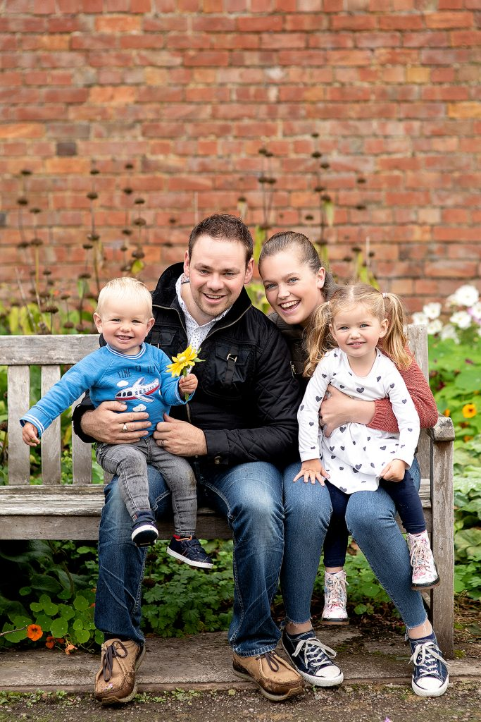 family of four sat on a outdoor bench enjoying a family photoshoot in Lisburn, Northern Ireland