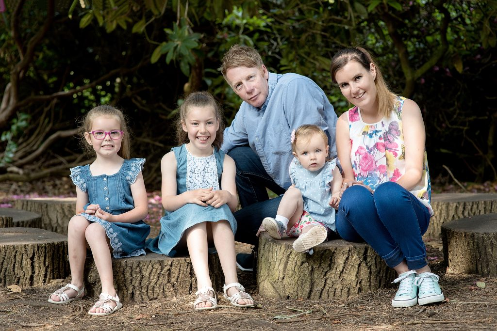 three daughters with their mother and father all sat on tree stubs