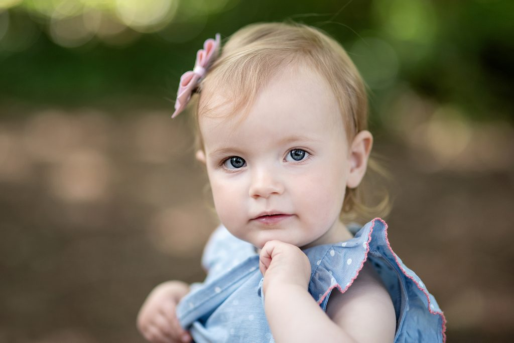lovely little blue eyed baby girl wearing a pink boy and blue dress
