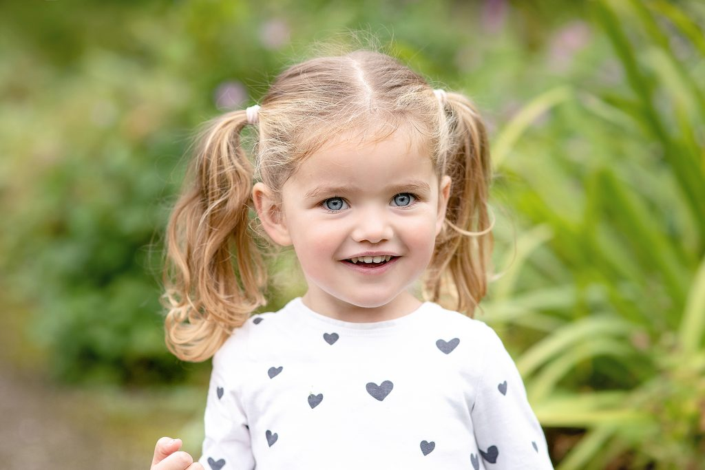 Blue eyed little girl with blonde pigtails wearing a polka heart top