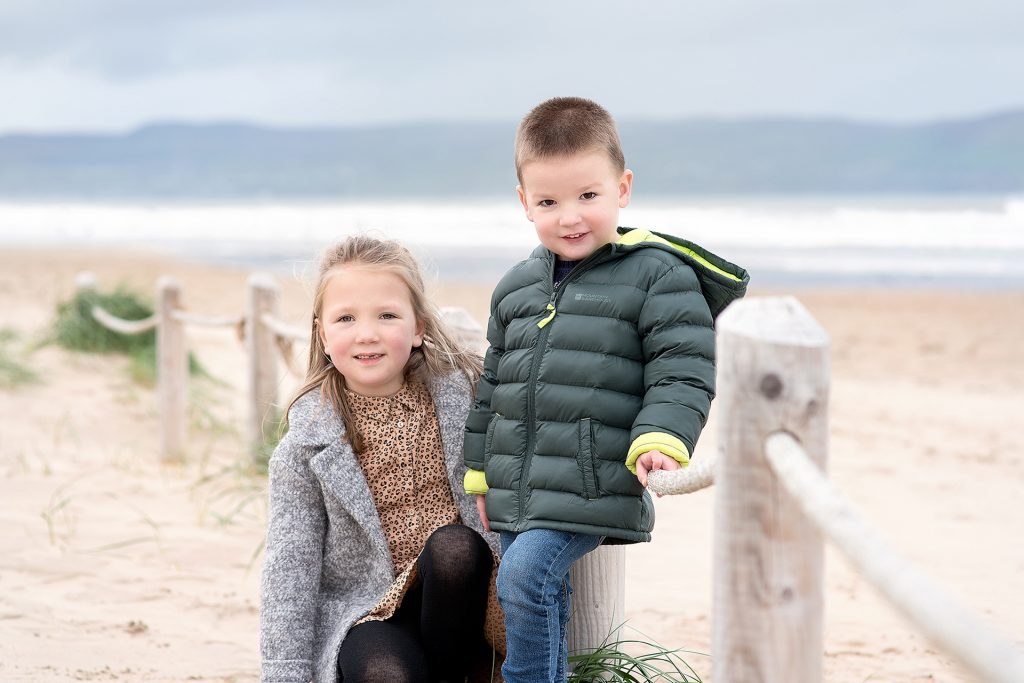 boy and sister sat on the beach in Northern Ireland