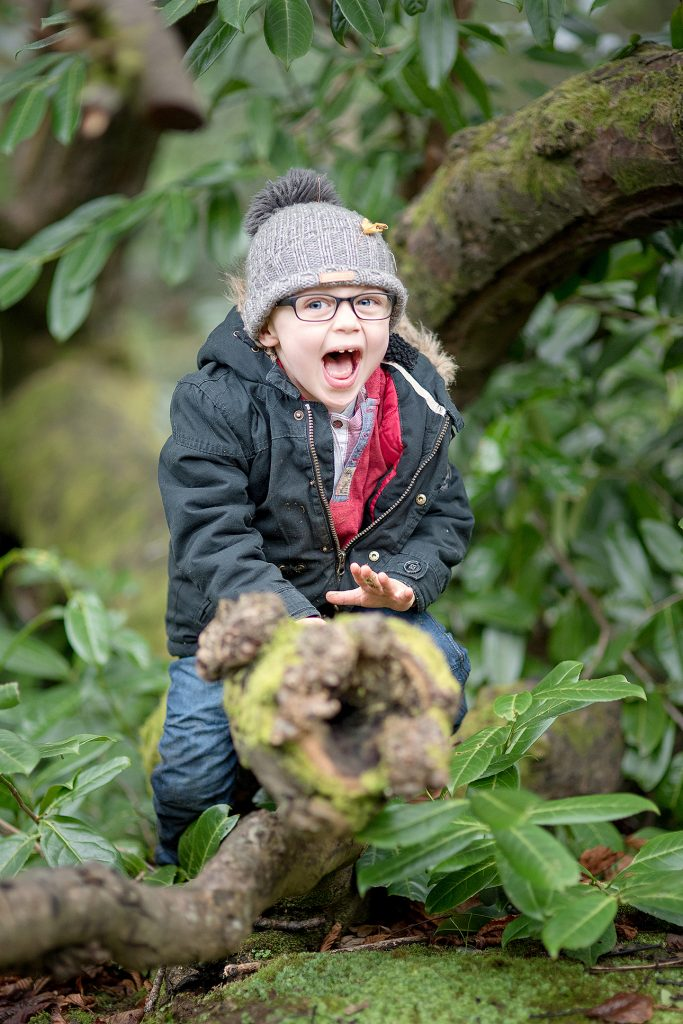 Gorgeous little boy with autumn clothing on sat on a tree branch