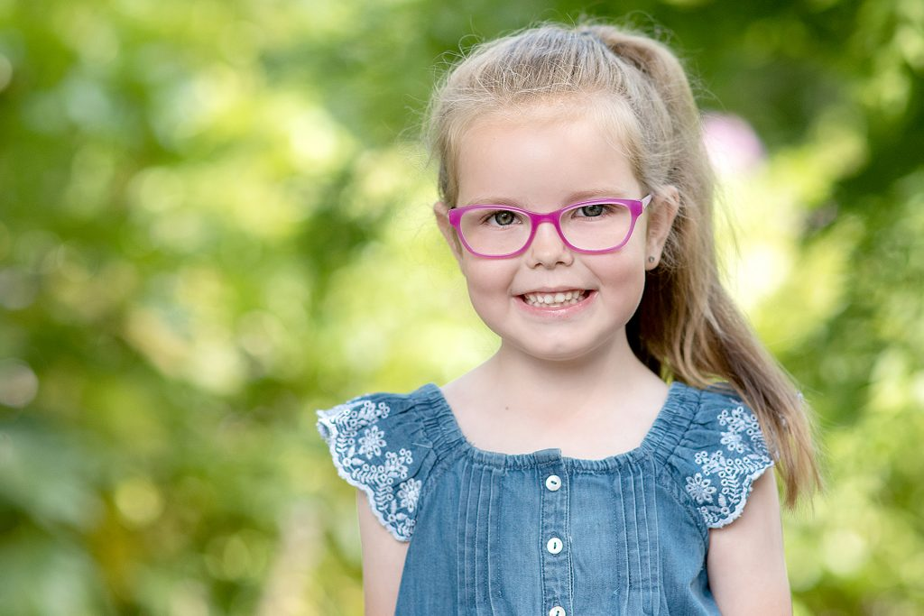 Stunning little girl in denim amongst the trees in Northern Ireland