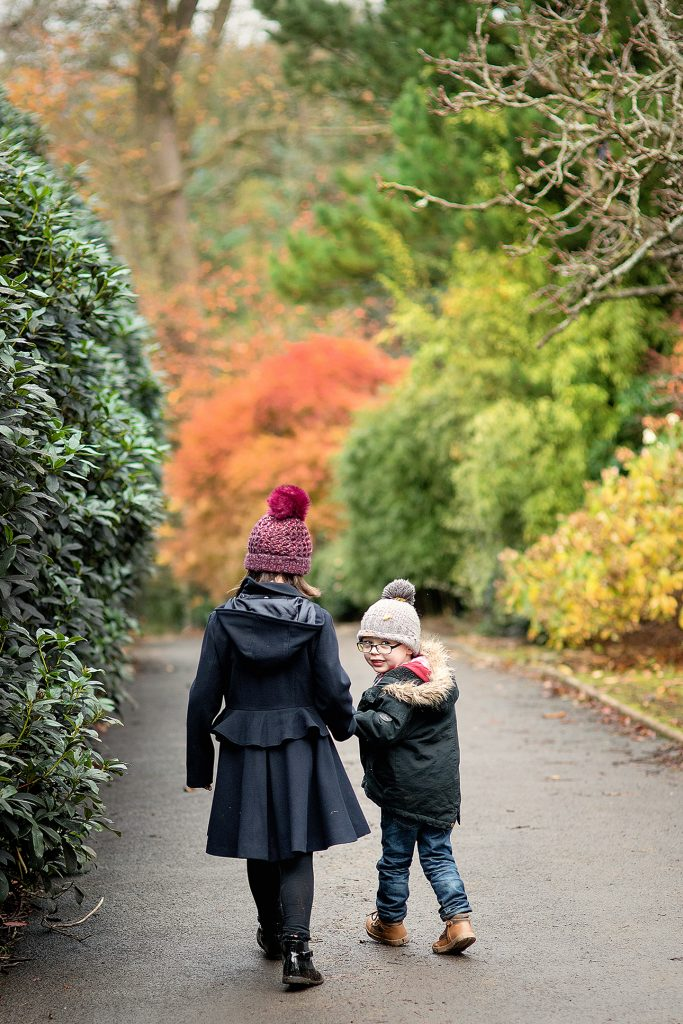young brother and his older sister holding hands and walking through the park