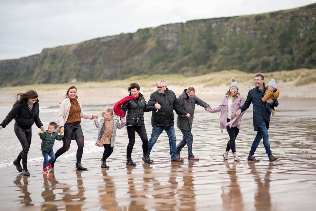 Large family walking along the beach posing for a photo professionally taken by Kelly McCambley