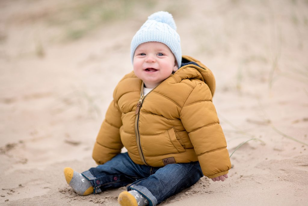 cute baby wearing a warm yellow jacket sat on a sandy beach in Northern Ireland