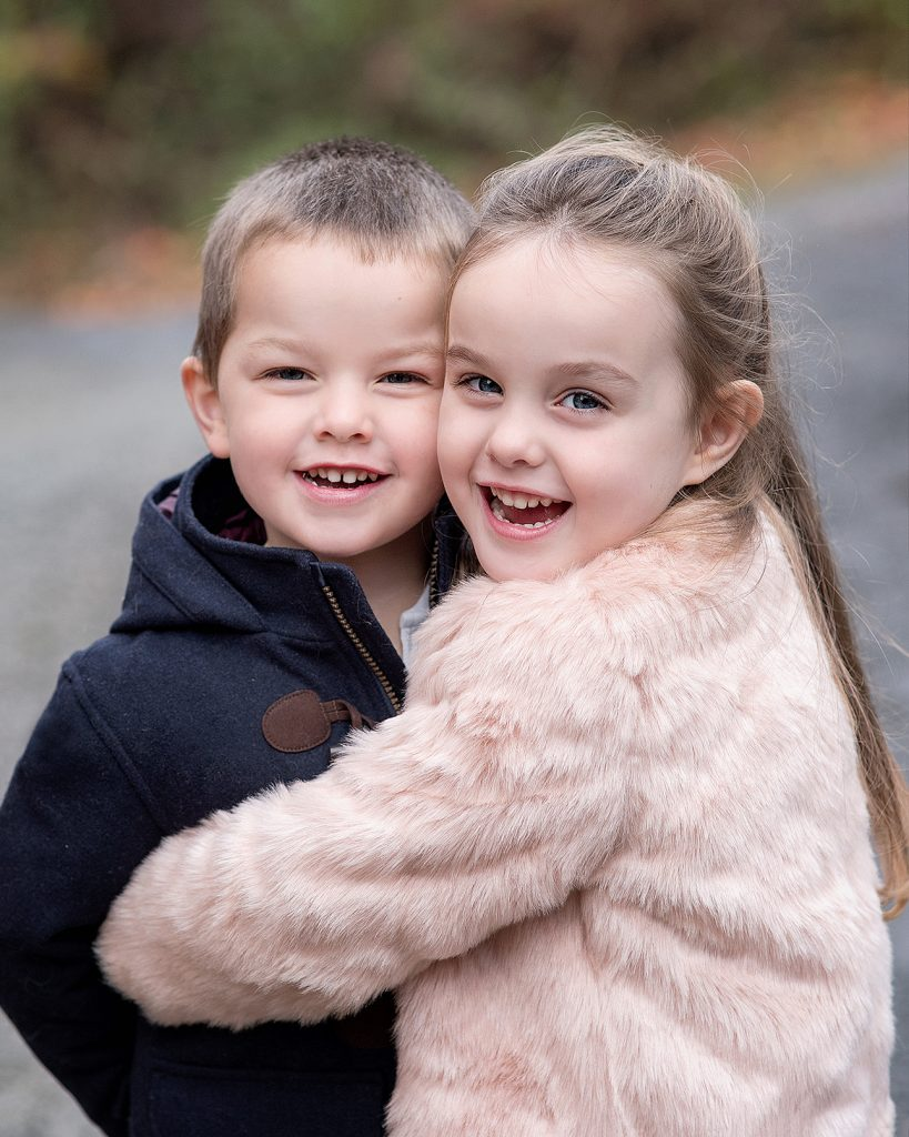 brother and sister children hugging each other outside photoshoot