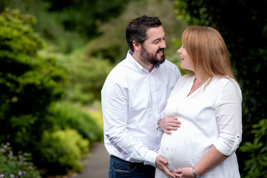 father to be and mother to be cupping her pregnant belly