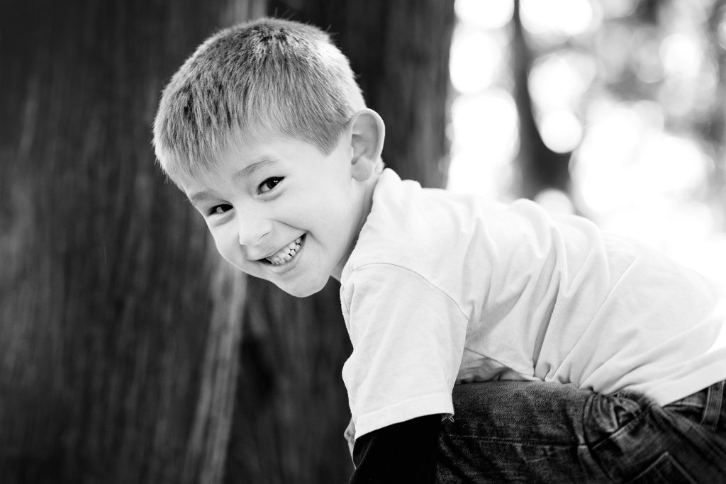 black and white shot of a young boy looking directly into the camera outdoors
