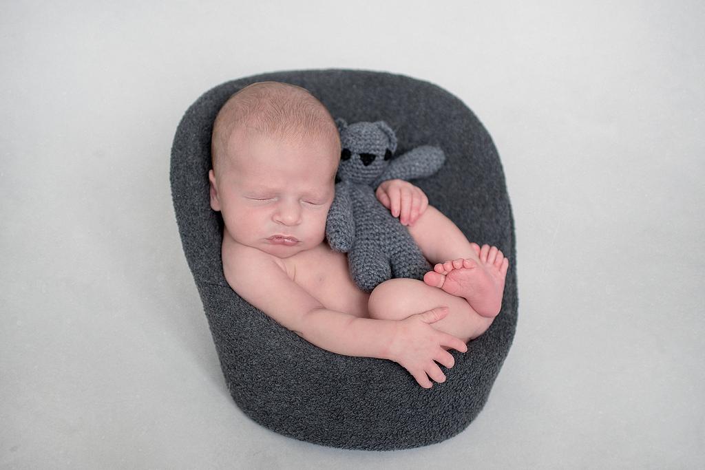 newborn sleeping on a baby sofa with a grey teddy bear