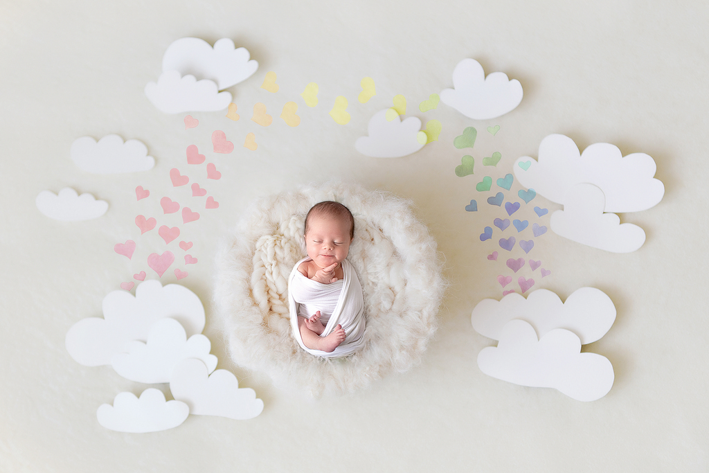little newborn sleeping on a cloud surrounded by cloud props and a rainbow of hearts