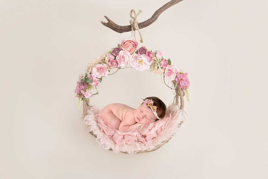 little girl hanging in a floral basket from a branch
