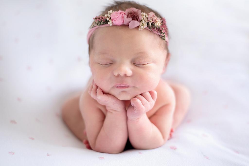 baby asleep with her head being held in her hands