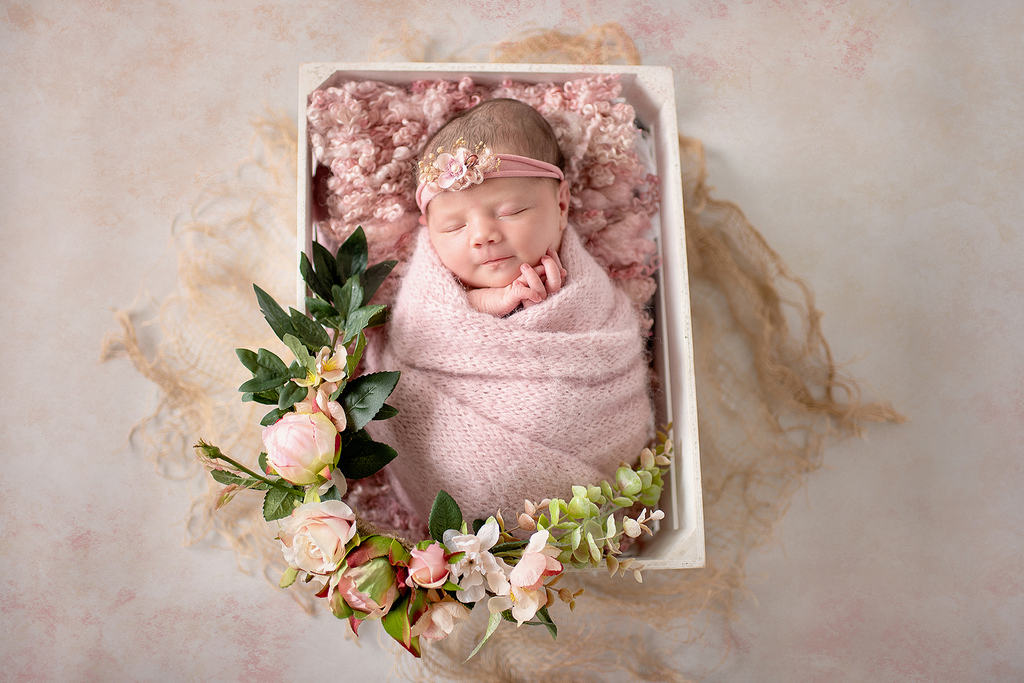 baby sleeping in a pink padded wooden crate