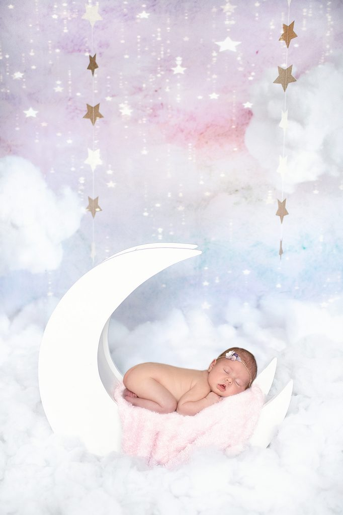 stunning studio photo of the moon and the stars and a baby sleeping among them