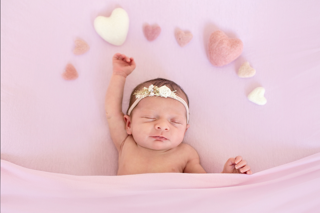 little newborn baby girl stretching out right arm towards a white fluffy heart