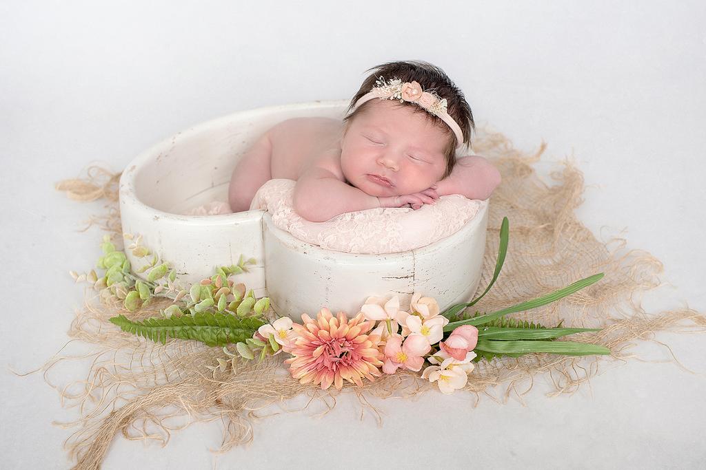 little newborn baby sleeping in a heart shaped bowl