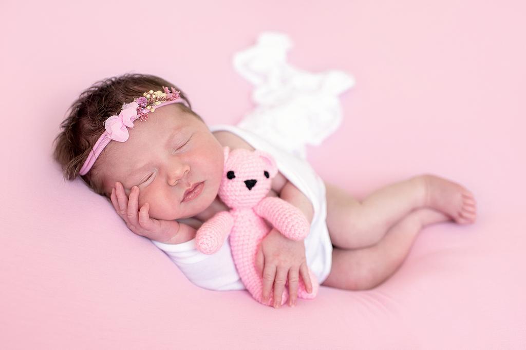 newborn baby cuddling a pink teddy bear - professional newborn photography by Kelly McCambley