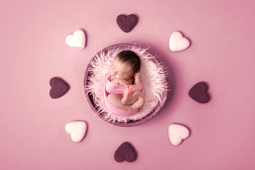 pink setting with newborn baby and hearts