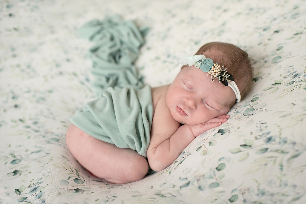 little baby asleep on a teal floral setting