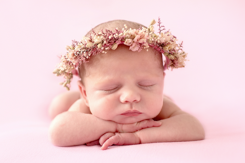close up of newborn sleeping with pink background
