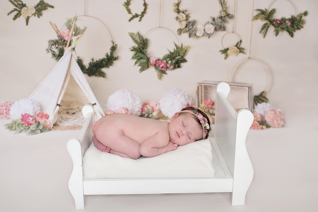 newborn baby sleeping in a small bed in a newborn studio