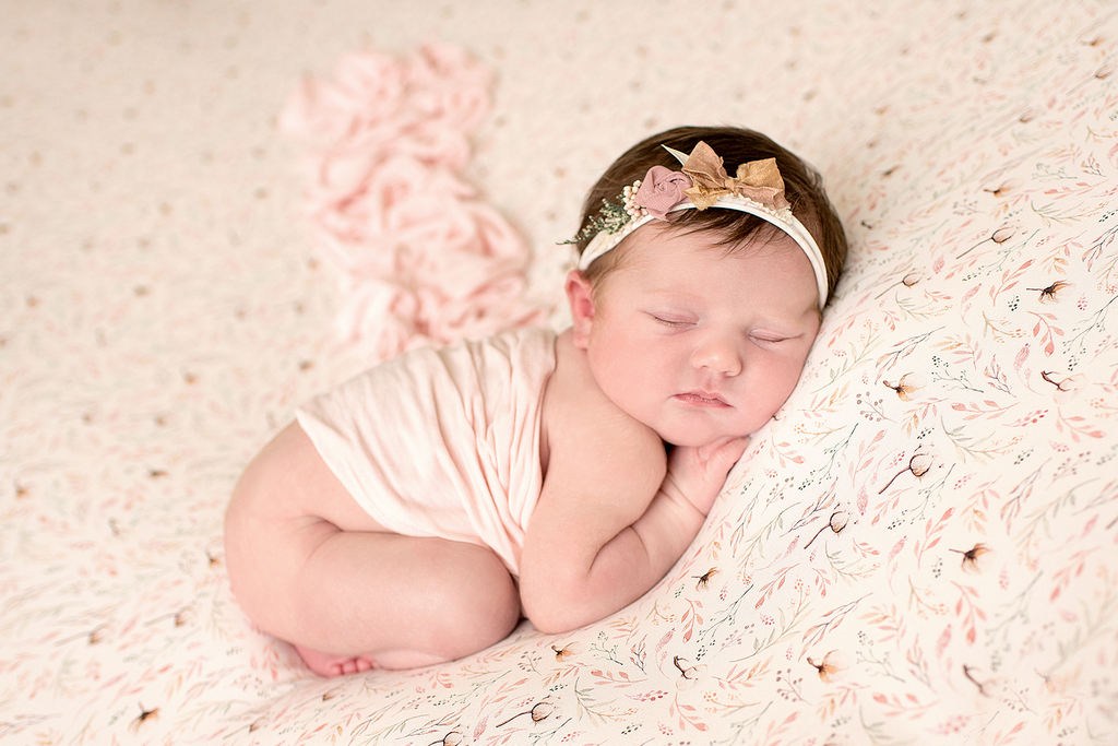 newborn baby girl sleeping soundly with a silk scarf draped over her