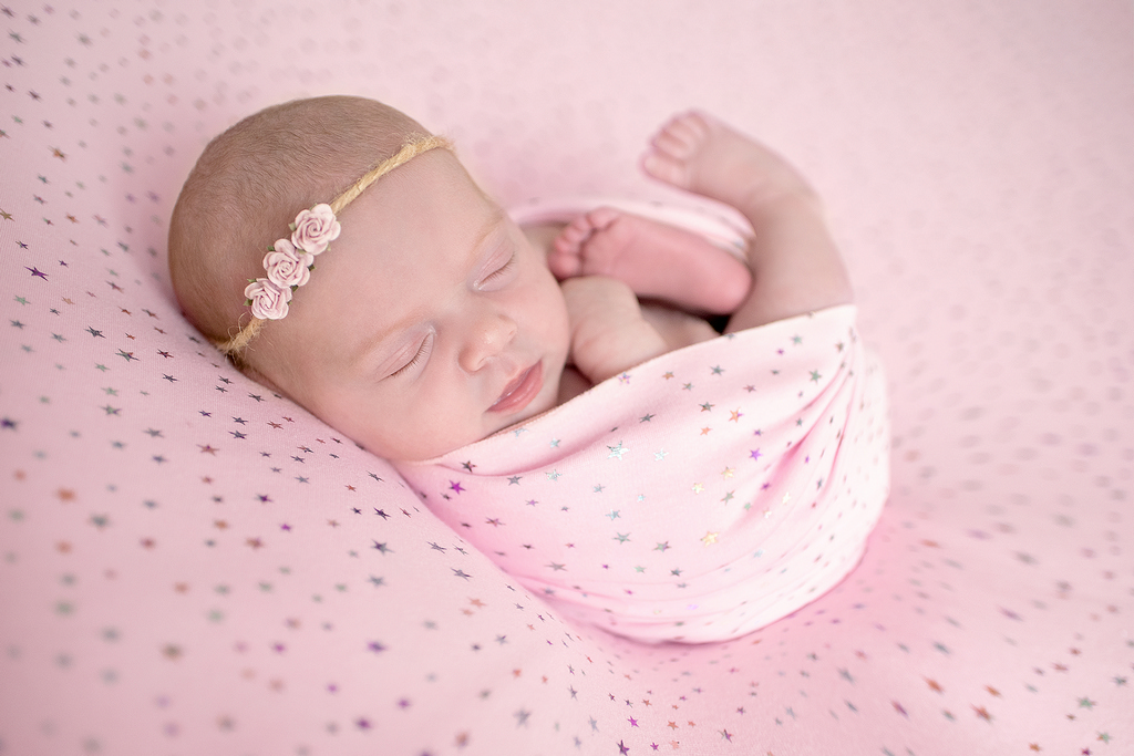 newborn in a pink and starry quilt