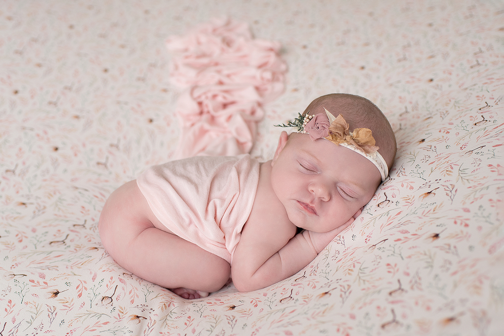 newborn sleeping soundly on a floral bed
