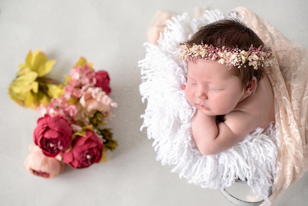 Little newborn wearing a floral headband sleeping soundly in a bucket