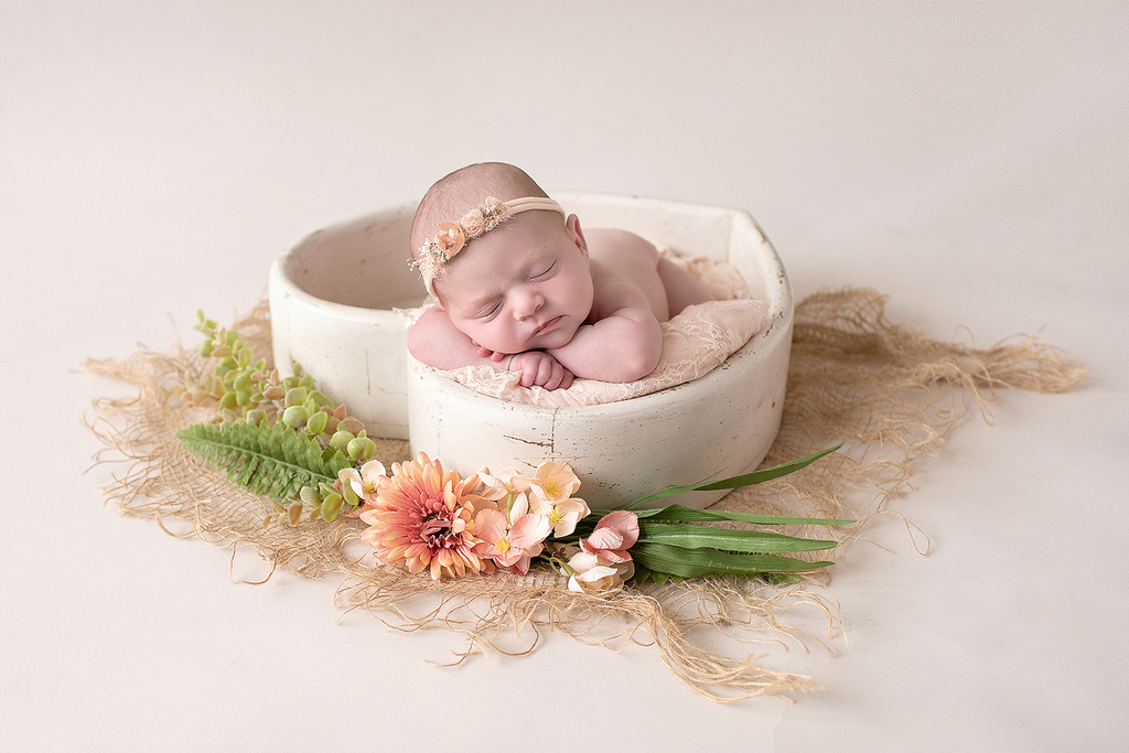 Heart shaped bowl studio setting with a newborn baby sleeping in it