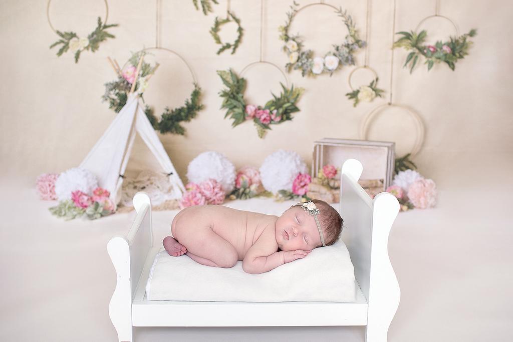 Newborn baby asleep on a tiny bed designed for newborns