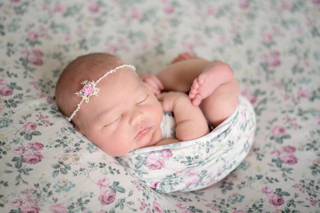 little newborn baby girl asleep with flowers surrounding her